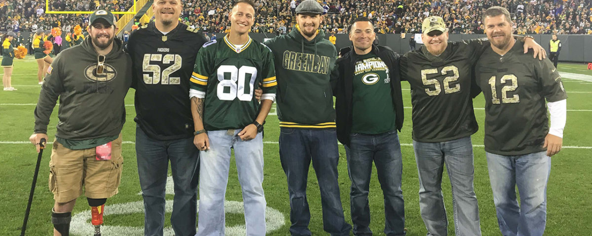 Standing on the field are, left to right: Jeremy Stengel, Jason Johns, Gregory Haak, Kevin Hanrahan, Andrew Diaz, Tim La Sage of WPS, and Scott Kruchten. (La Sage, who helped organize the recognition, was among those honored by Operation Fan Mail in 2015. He is a Marine Corps veteran and recipient of two Purple Hearts.)