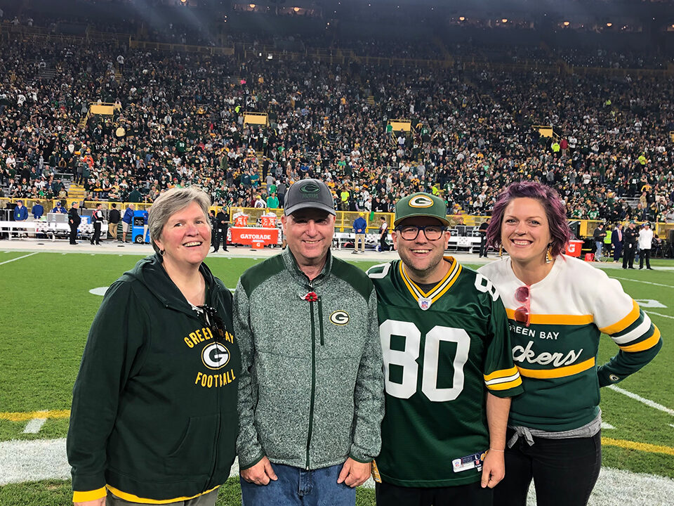Army veteran Mike Klas is shown on the field with his wife, Joyce; son, Kevin; and daughter-in-law, Christina. (Photo by Katie Hermsen/Green Bay Packers)