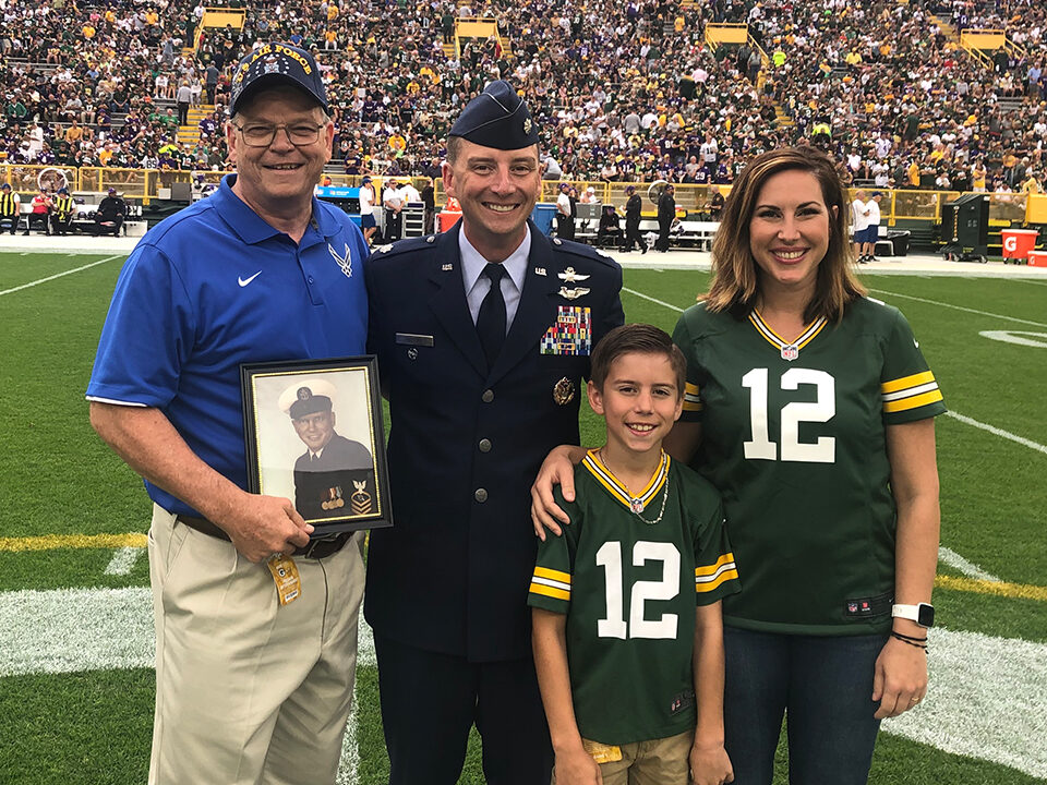 "Air Force Lieutenant Colonel John ""JJ"" Riester is shown on the field with his father, Scott Riester, his wife, Aimee, and their son, Scott. (Photo by Katie Hermsen/Green Bay Packers)"