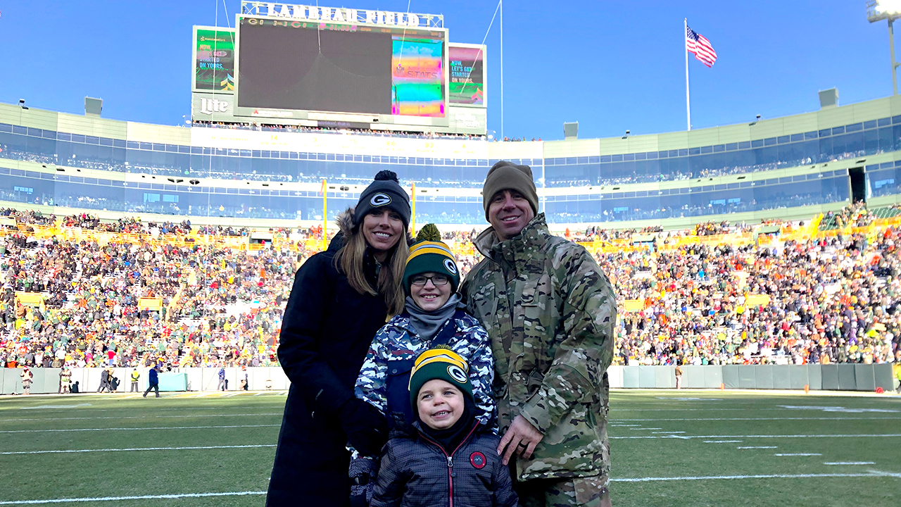 Chief Master Sergeant Aaron Thornsen is shown on the field with his wife, Nicole, and their sons, Phillip and Dominic (front).