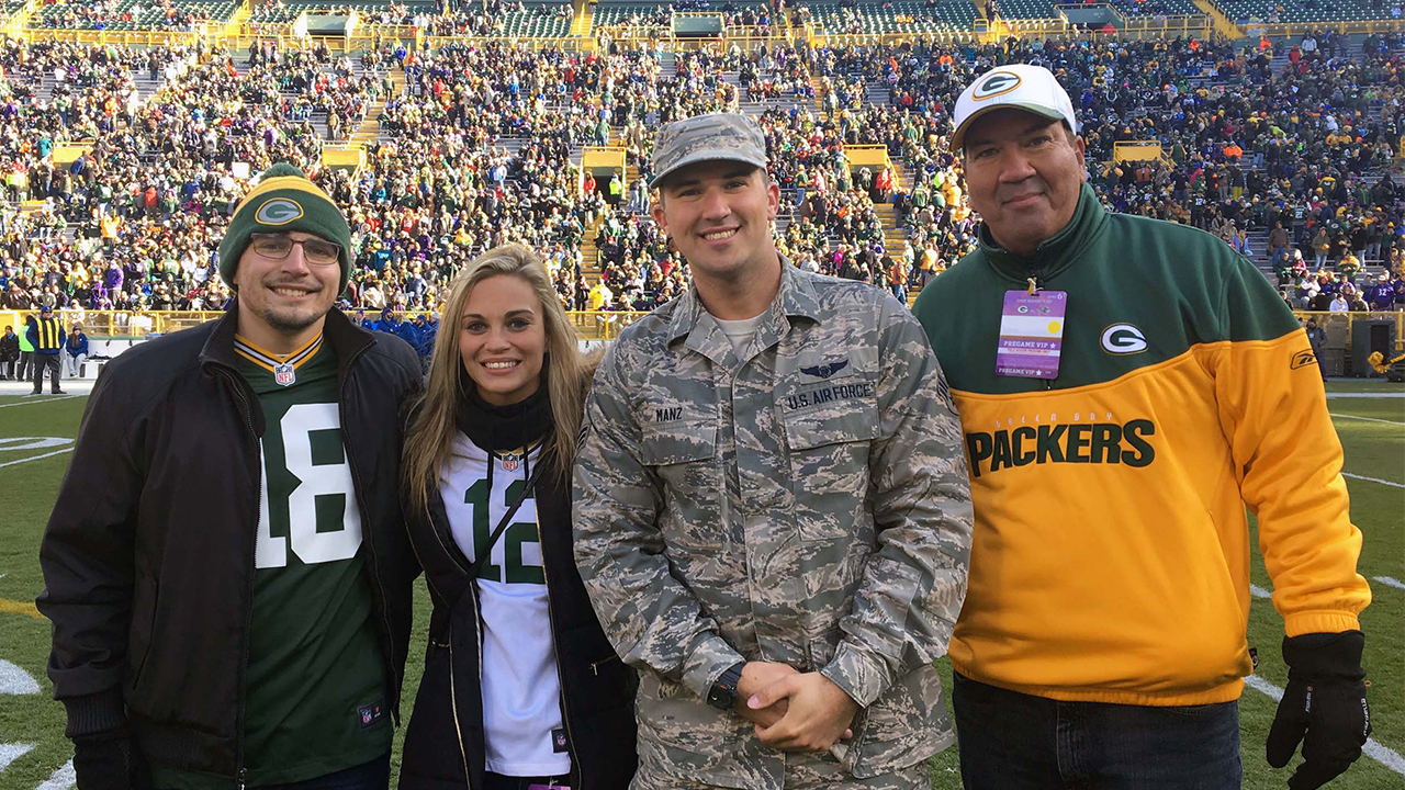 Senior Airman Taylor Manz is shown on the field before the game with his father, Mark (right), and friends Taylor Tomczak and Jenny Eickhorst.