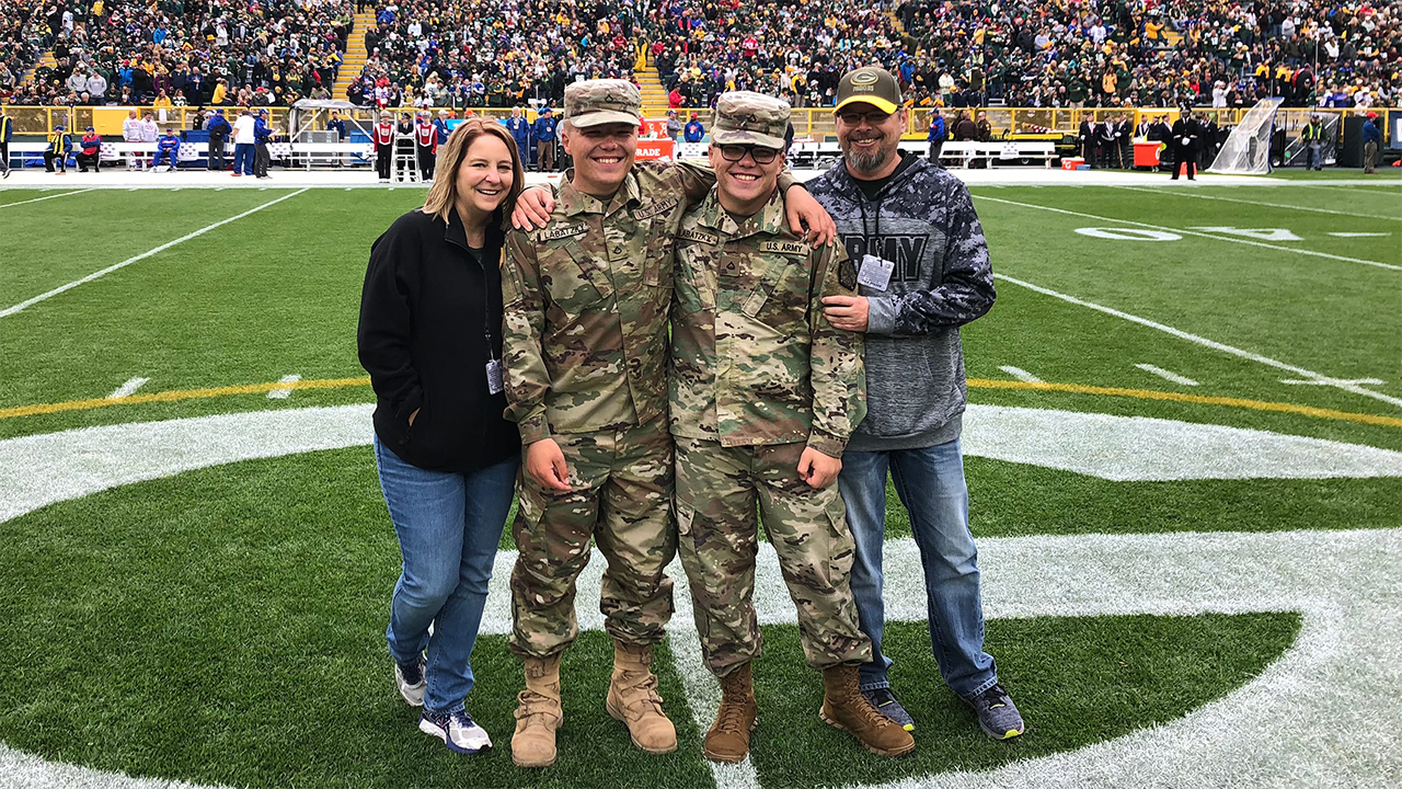 Trevor (second from left) and Nicolas Labatzky are shown on the field with their father, Tim Labatzky, and Tim's girlfriend, Shannon Knight.