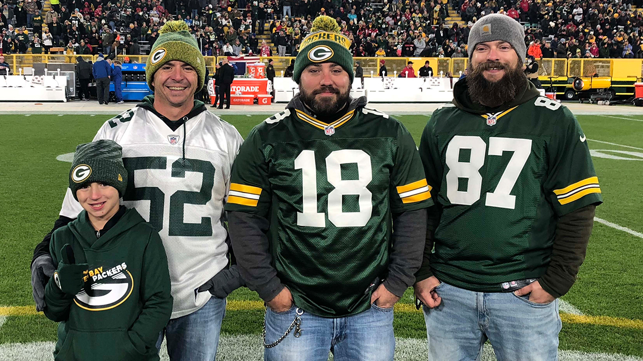 Operation Fan Mail honoree Dustin Crane (wearing the No. 18 jersey) is shown on the field with his friends, Mark Delano (left) and Dennis Kinchen (right), and Mark's son, Ryan.