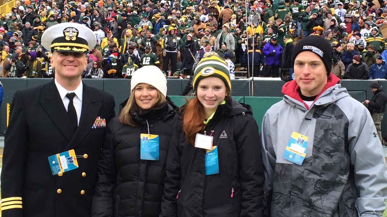 Standing on the field with Navy Reserve Nurse Corps Commander Eric Peterson are his wife, Jodi, and their daughter, Jenna, and son, Alex.