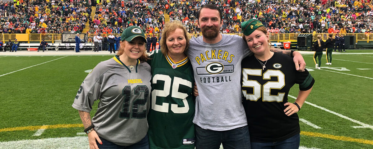 Marine Corps veteran Kim Graff (right) is shown on the field with her friend, Kit Amidzich (left); mother, Robin Shriver; and husband, Marine Corps Gunnery Sergeant William Graff. (Photo by Katie Hermsen/Green Bay Packers)