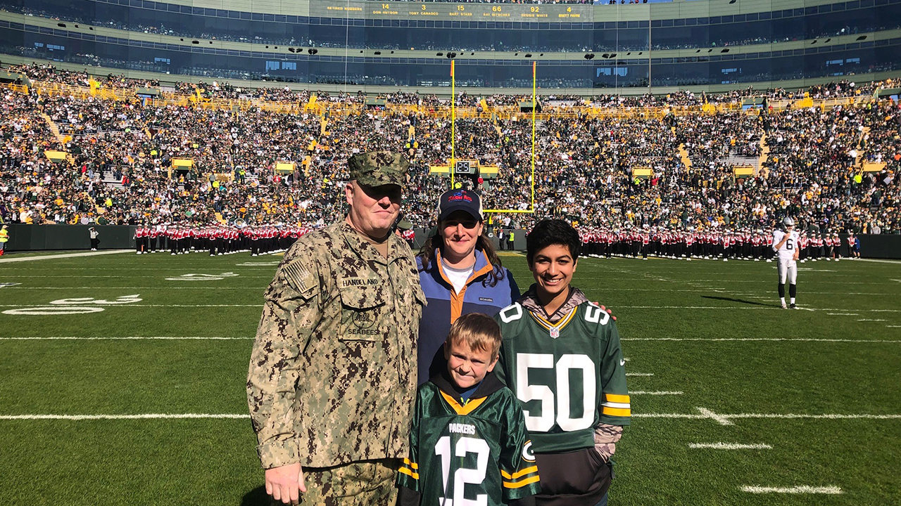 Andrew S. Handeland Sr. is shown on the field with his wife, Holly, and sons, Alejandro and Andrew Jr. (Photo by Katie Hermsen/Green Bay Packers)