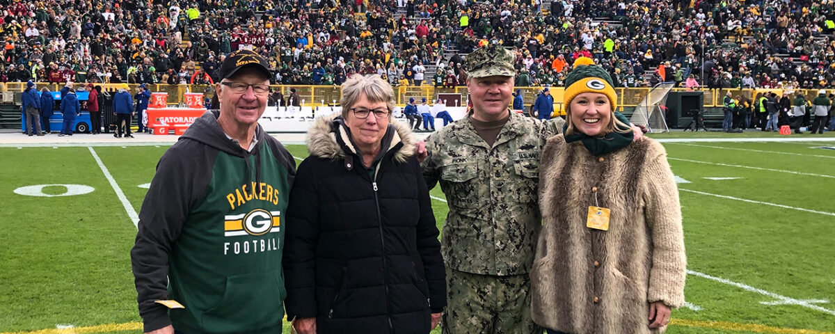 Senior Chief Petty Officer Jeremy Pionk is joined on the field by his wife, Janna, (right) and his parents, Duane and Sandy.